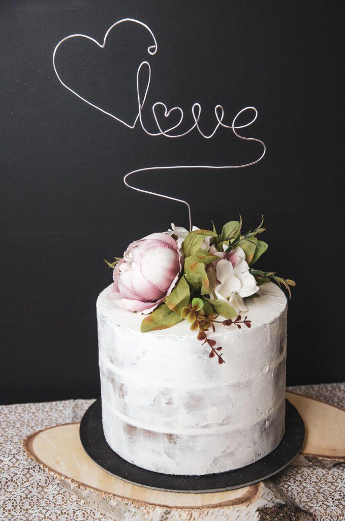 Fake Cake also eine unechte Torte mit Sahneschicht und Blumen oben drauf