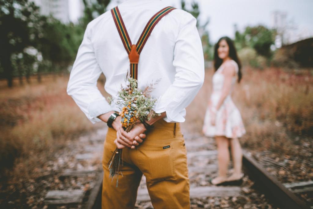 Mann mit Blumenstrauß hinter dem Rücken bereit für den perfekten Heiratsantrag