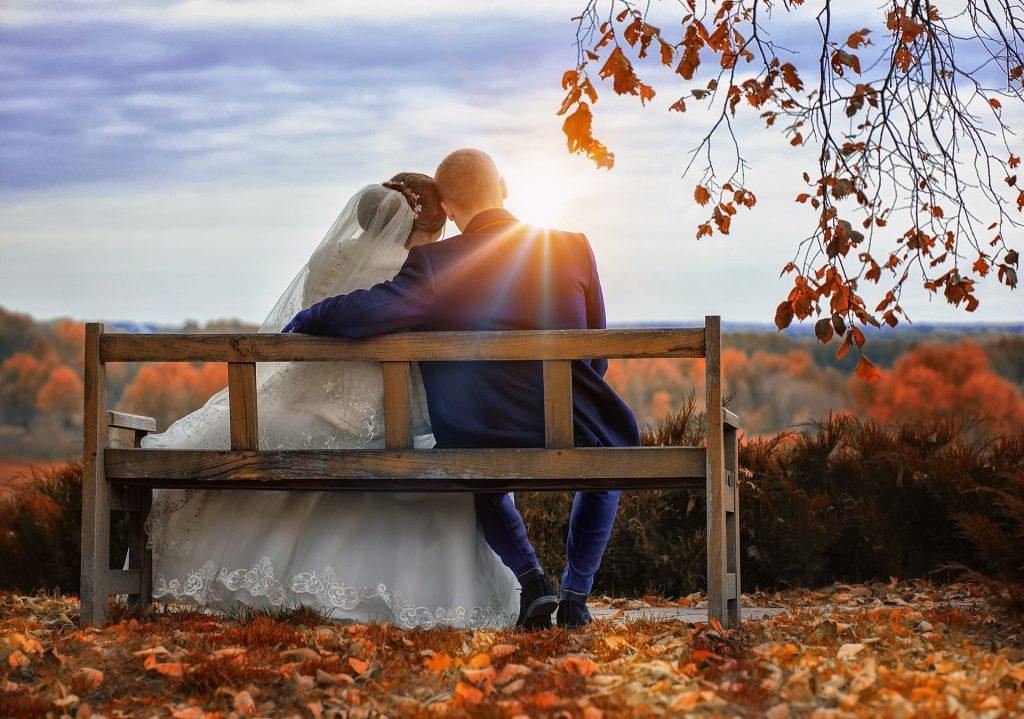 Brautpaar sitzt auf einer Bank im Herbstwald