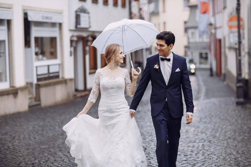 Brautpaar spaziert bei Regen durch die Straßen