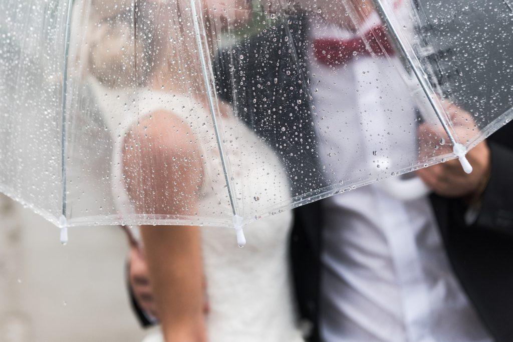 Brautpaar unter einem transparenten Regenschirm
