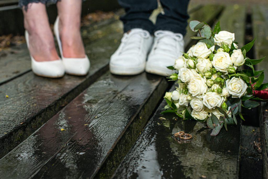 Eheringe mit Brautstrauß im Regen